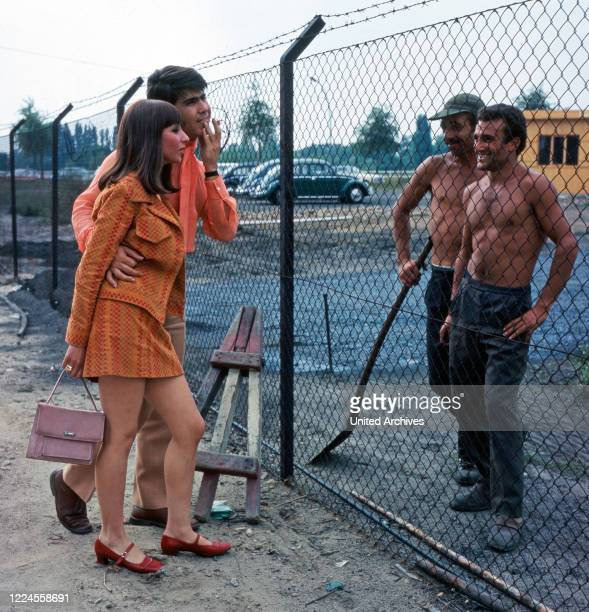 The musician couple Esther Abi Ofarim talks to two construction workers who are staying behind a fence in Berlin Germany 1967