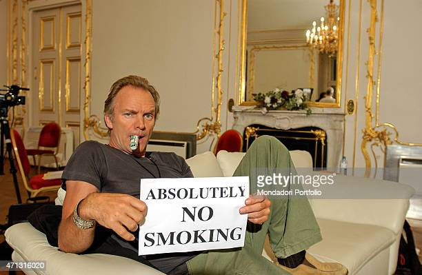 The musician Sting showing a sign saying that smoking is forbidden during a photo shooting Wien Austria 15th June 2004