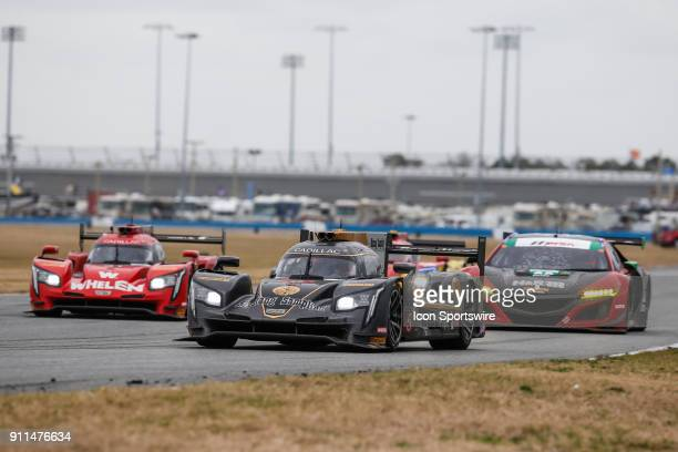 The Mustang Sampling Racing Cadillac DPiVR of Filipe Albuquerque Joao Barbosa and Christian Fittipaldi leads a pack of cars into a turn during the...