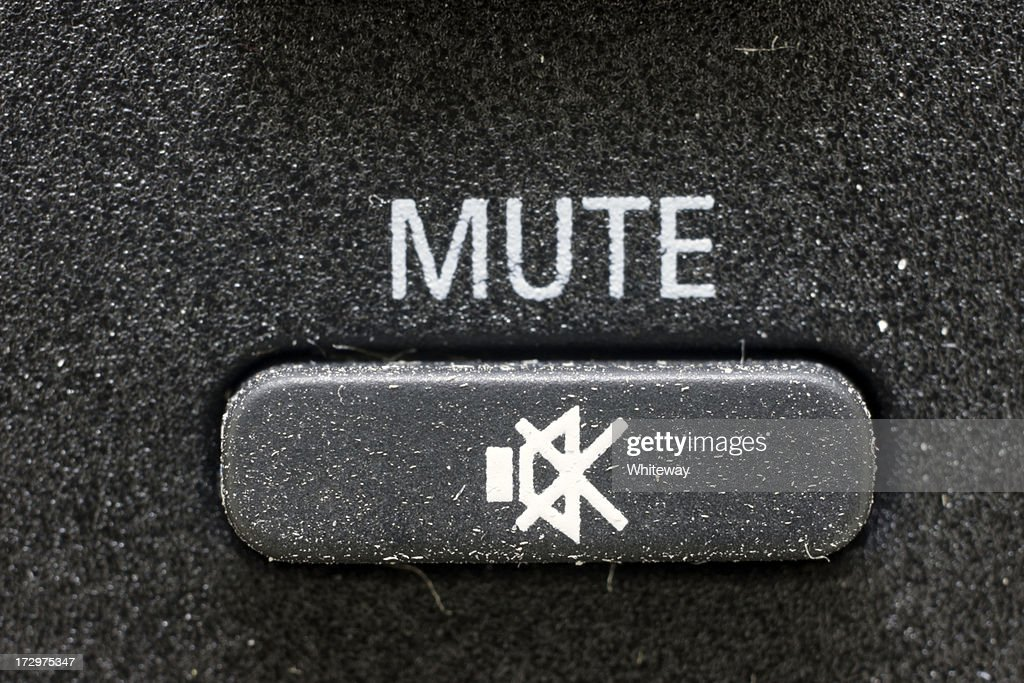 Mute button on black rubber TV remote control magnified : Stock Photo
