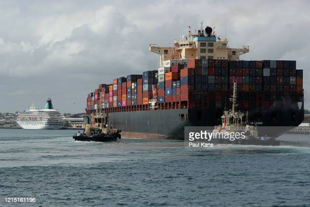 The MV Artania is seen berthed at the Fremantle Passenger Terminal as the container ship Maersk Semarang is assisted into the harbour by tugs on...