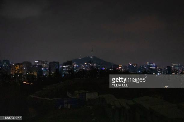 The N Seoul Tower and the historic Seoul Fortress Wall are seen after their lights went out for the Earth Hour environmental campaign in Seoul on...