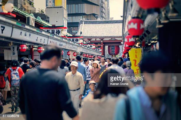 The Nakamise Shopping Street with many tourists shopping Asakusa Tokyo Japan The Kaminarimon gate can be seen with it's famous red lantern