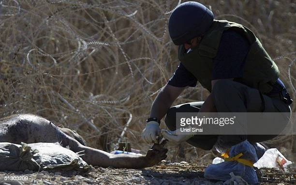 The naked body of a suicide bomber has finger prints taken by an Israeli border police offier near an Israeli Defence Force checkpoint September 14...