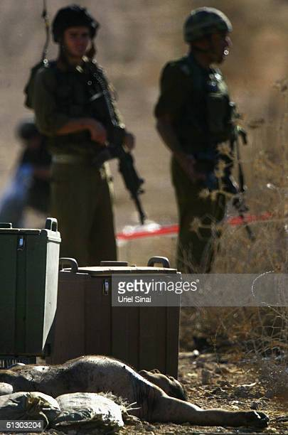 The naked body of a suicide bomber lays on the ground as Israeli soldiers look on near an Israeli Defence Force checkpoint September 14 2004 near the...