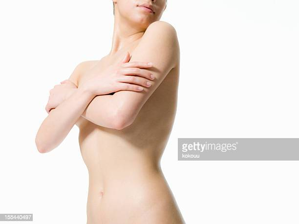 The naked woman holds her arm