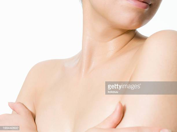 The naked woman holds her upper arm with a smile