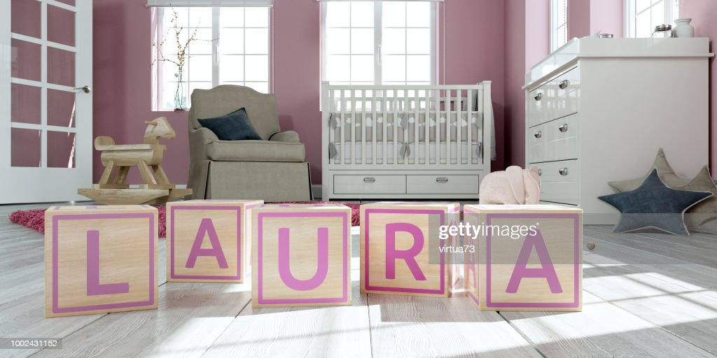 The name laura written with wooden toy cubes in children's room : Stock Photo