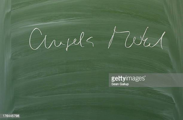 The name of German Chancellor Angela Merkel is visible on a chalkboard after she wrote it there while speaking to 12th grade high school students...