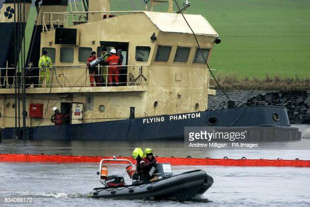 The name of the boat Flying Phantom Tug is visible as the barge GPS Atlas continues its salvage operation on the river ClydeThe Flying Phantom tug...