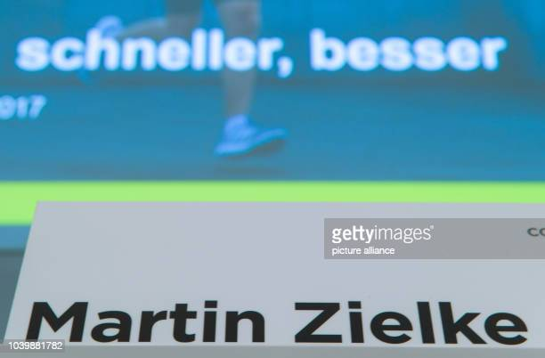 The nameplate of Commerzbank CEO Martin Zielke can be seen in front of a projection showing the words 'faster better' at the press conference...