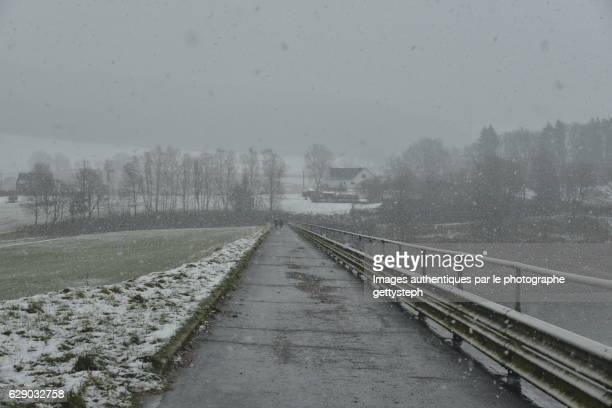 the narrow road at the top of dirt dam under intense snow fal - ardennes department france stock photos and pictures