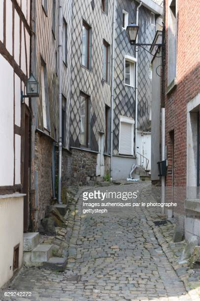 the narrow slope alley between old facades - ardennes department france stock photos and pictures