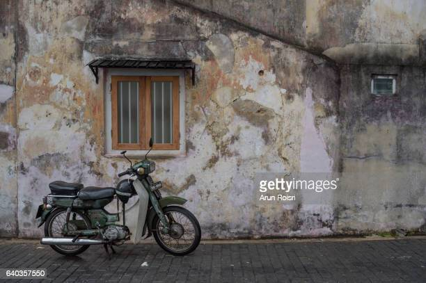 The narrow street of Galle Fort with parked classic motorcycle, Sri Lanka.