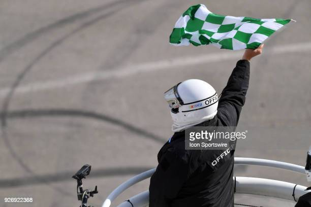 The NASCAR official waves the green and white checkered flag signaling the end of a stage during the NASCAR Xfinity Series Boyd Gaming 300 on March...