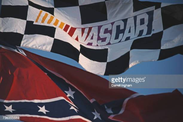 The NASCAR Series flag flies alongside the old Confederate Stars and Bars battle flag during the NASCAR Winston Cup Series Primestar 500 race on 9...