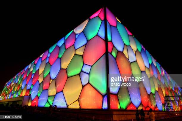 The National Aquatics Center also known as the Water Cube is illuminated with multicolours as people have their pictures taken in Beijing on August 7...