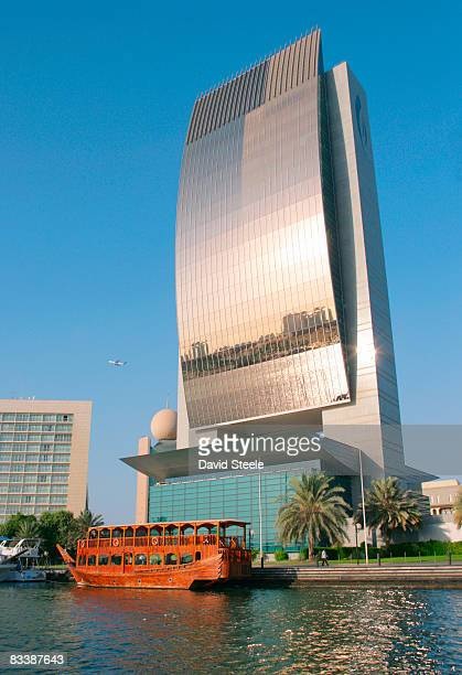 the national bank of dubai building with a wooden restaurant dhow moored in front of it, city of dubai, emirate of dubai, united arab emirates. - uae national day stock photos and pictures