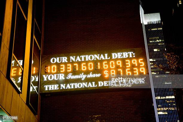 the national debt clock illuminated at night. - national debt clock stock photos and pictures