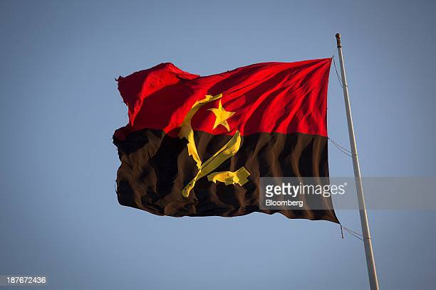 The national flag of Angola flies from the fort museum in Luanda Angola on Friday Nov 8 2013 Angola the largest crude oil producer in Africa after...