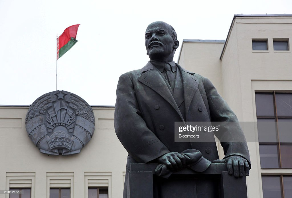 The national flag of Belarus flies on a state building above a statue of former Communist Party founder Vladimir Lenin on Independence square in Minsk, Belarus, on Wednesday, March 16, 2016. European Union governments scrapped sanctions on leaders of Belarus in an effort to pry the former Soviet republic out of the shadow of the Kremlin. Photographer: Andrey Rudakov/Bloomberg via Getty Images