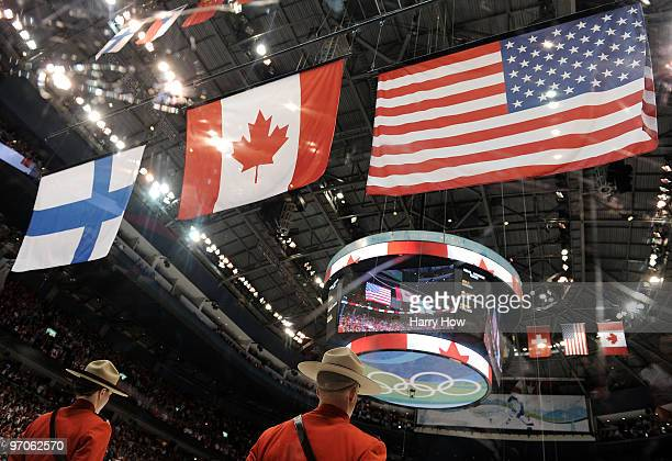The national flag of Canada flies above those of the USA and Finland during the medal ceremony following the ice hockey women's gold medal game...