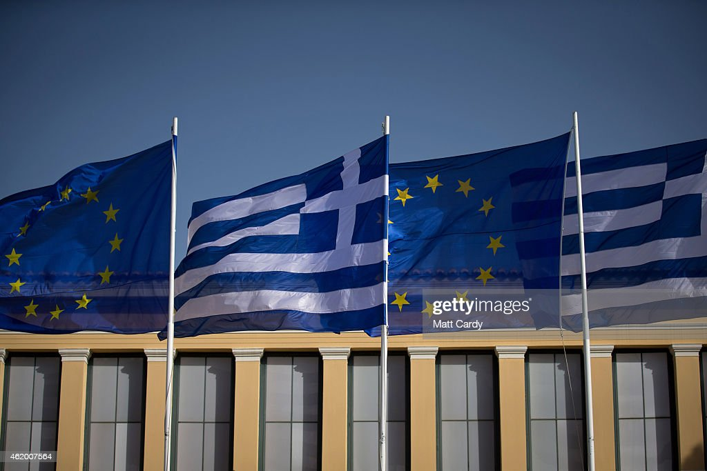 The national flag of Greece and the flag of the European Union fly above a government building ahead of the general election on Sunday on January 23, 2015 in Athens, Greece. According to the latest opinion polls, the left-wing Syriza party are poised to defeat Prime Minister Antonis Samaras' conservative New Democracy party in the election, which will take place on Sunday. European leaders fear that Greece could abandon the Euro, write off some of its national debt and put an end to the country's austerity by renegotiating the terms of its bailout if the radical Syriza party comes to power. Greece's potential withdrawal from the eurozone has become known as the 'Grexit'.