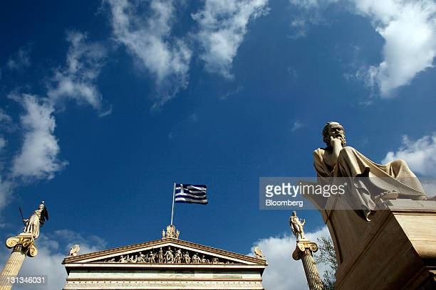 The national flag of Greece flies near sculptures of ancient Greek philosophers at Athens University in Athens Greece on Thursday Nov 3 2011 Prime...