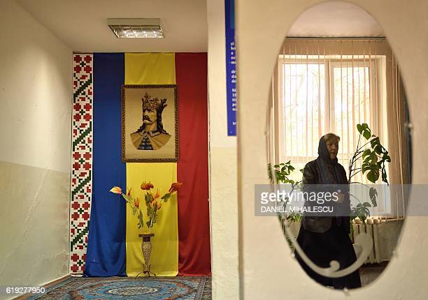 The national flag of Moldova with a picture of King Stephen III of Moldavia is seen as a voter arrives at a polling station in Sireti village,...