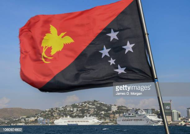 The national flag of PNG flies in front of PO's Pacific Explorer and Pacific Jewel berthed on November 13 2018 in Port Moresby Papua New Guinea...