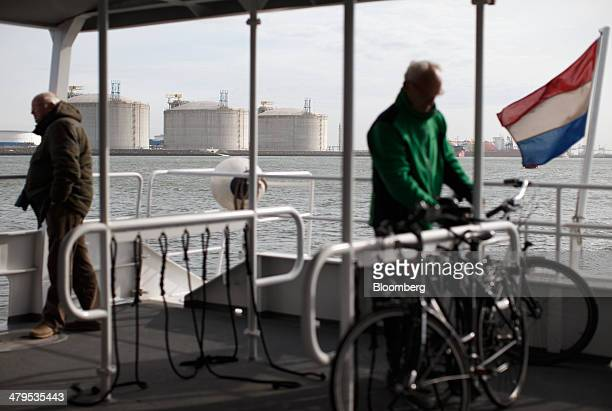 The national flag of the Netherlands flies from a sightseeing ferry as liquid natural gas storage tanks stand beyond on the shoreline at the Gate LNG...