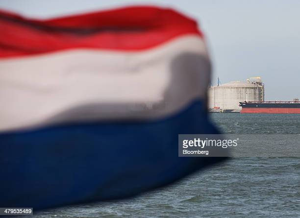 The national flag of the Netherlands flies from a sightseeing ferry as liquid natural gas storage tanks and the crude oil tanker Petalidi are seen...