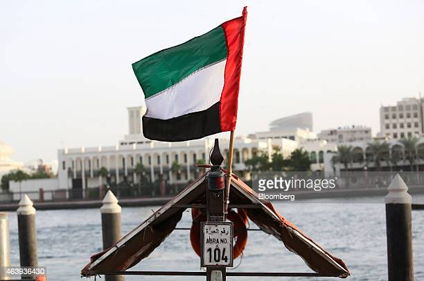 The national flag of the UAE flies from a water taxi also known as an abra on the waterway in Al Ghubaiba's creek district of Dubai United Arab...
