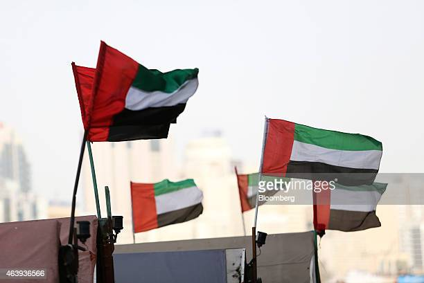 The national flag of the UAE flies from water taxis also known as abras on the waterway in Al Ghubaiba's creek district of Dubai United Arab Emirates...