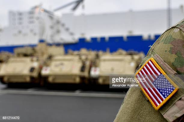 The national flag of the United States of America is pictured on a worker unloading US Army M1 Abrams and Bradley Fighting Vehicles onto trains after...