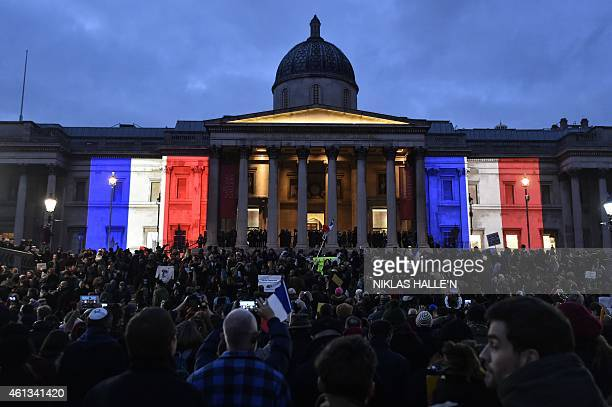 The National Gallery is lit up in the colours of the French flag as crowds gather in Trafalgar Square in central London on January 11 2015 to...