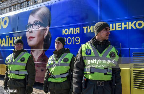The National guard servicemen guard a bus bearing an image of the former Ukrainian Prime Minister and presidential candidate Yulia Tymoshenko in Kiev...