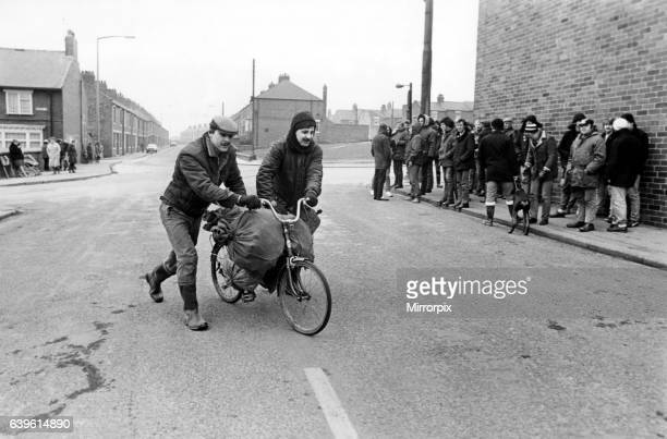 The National Miners Strike 1985 Easington coal delivery striking miners push a bike loaded with sea coal past a group of fellow strikers 13 February...