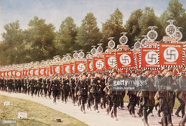 The National Socialist German Workers or Nazis attend a party rally at Nuremberg carrying standards bearing Swastikas and the slogan 'Deutschland...