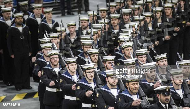 The naval honour guard marches onto the hangar deck during the Commissioning Ceremony for the Royal Navy aircraft carrier HMS Queen Elizabeth at HM...