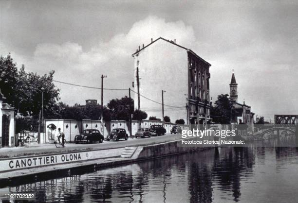"""The Naviglio Grande, in front of the headquarters and the landing of the """"Canottieri Olona"""". Photographic postcard, Italy, Milan 1957."""