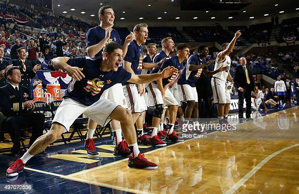 The Navy Midshipmen bench celebrates scoring a basket against the Florida Gators in the first half during the Veterans Classic at Alumni Hall on...
