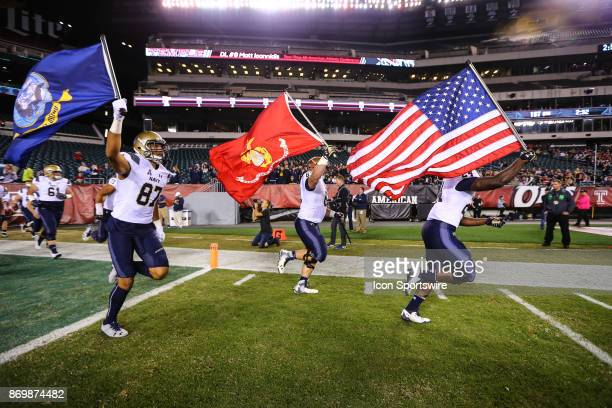 The Navy Midshipmen enter the field with an American Flag a Marine Corp flag and the Navy flag prior to the American Athletic Conference football...