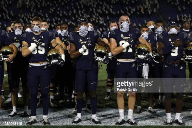 The Navy Midshipmen wear face coverings as they stand and salute during their fight song after losing to the Houston Cougars, 37-21, at Navy-Marine...