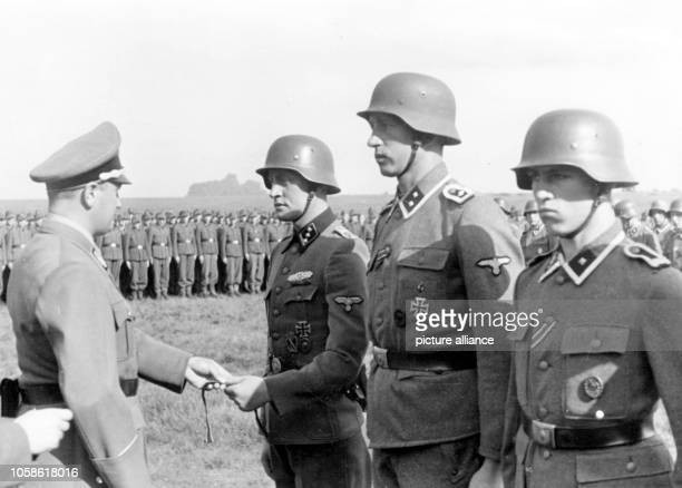 The Nazi propaganda image depicts German Nazi national leader of the Hitler Youth, Artur Axmann awarding the cuff title to members of the SS Panzer...