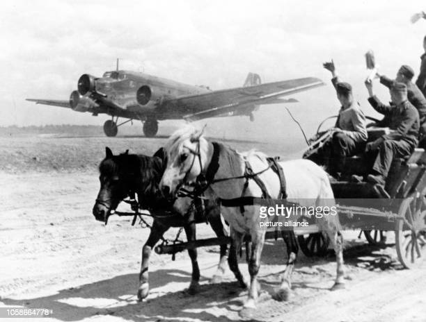 The Nazi propaganda image depicts soldiers of the German Wehrmacht on a horsedrawn vehicle with a starting transport aircraft type Junker Ju 52 on an...