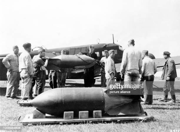 The Nazi propaganda image depicts soldiers of the German Wehrmacht standing around bombs in front of a transport combat type Junker Ju 52 on an...