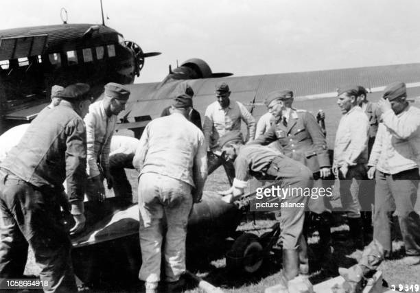 The Nazi propaganda image depicts soldiers of the German Wehrmacht standing around a bomb in front of an airfreighter type Junker Ju 52 on a...