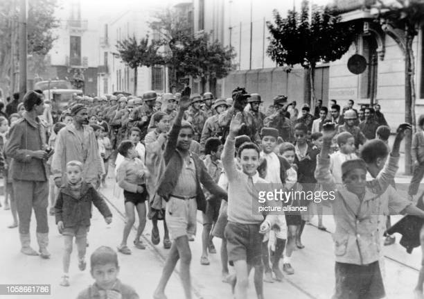 The Nazi propaganda picture shows local children making the Nazi salute during a march of German soldiers in the occupied city Tunis Tunisia February...