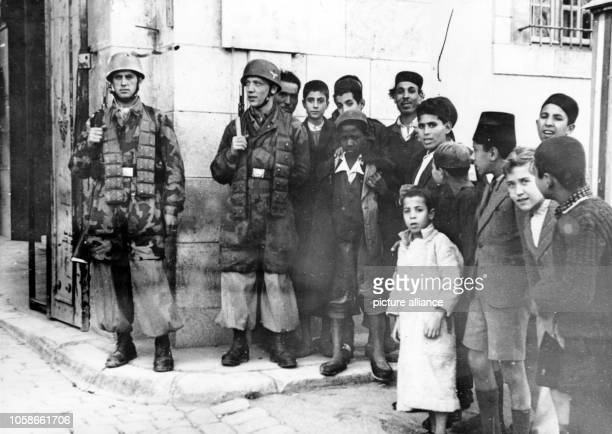The Nazi propaganda picture shows local children next to paratroopers of the German Wehrmacht in the occupied city Tunis in Tunisia The photo was...